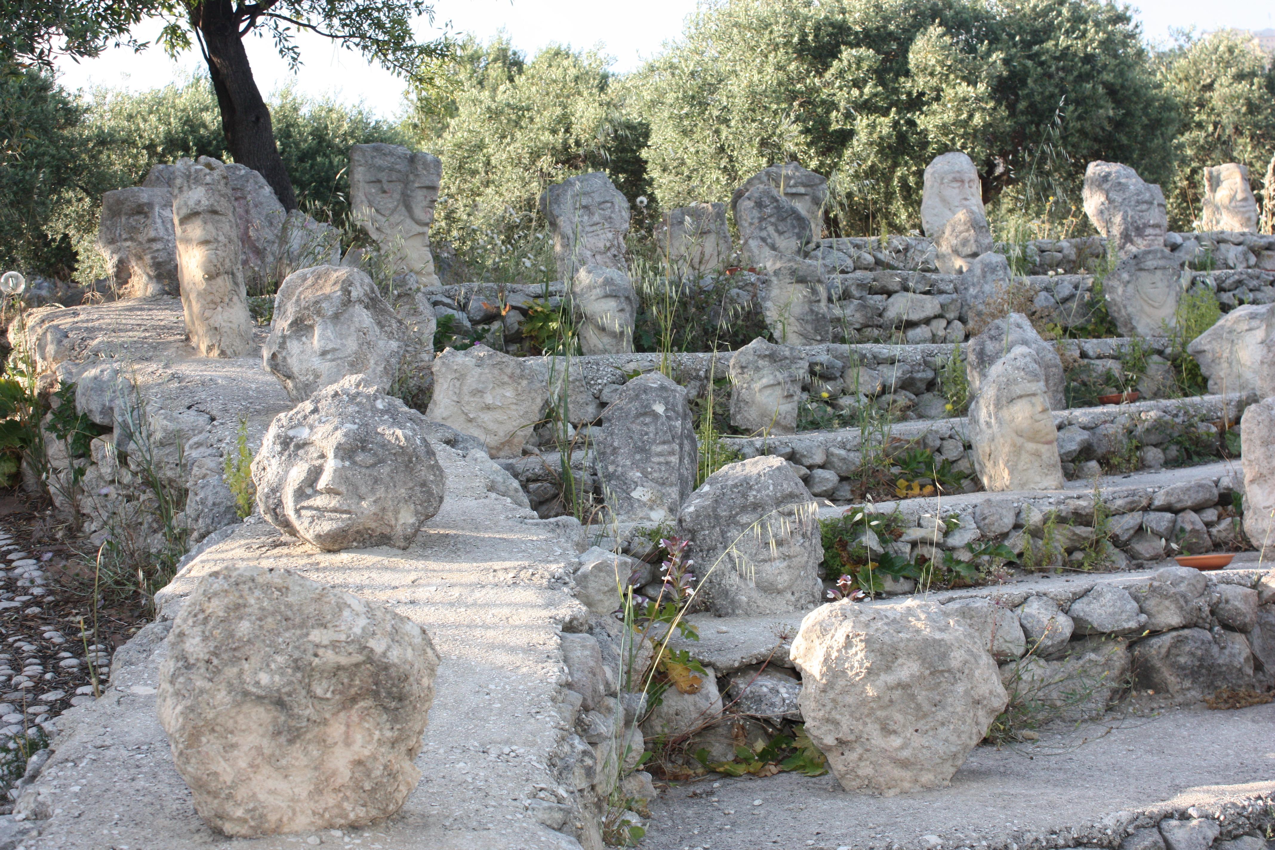 Castello Incantato estão em exposição centenas de cabeças esculpidas em pedra espalhadas no campo.